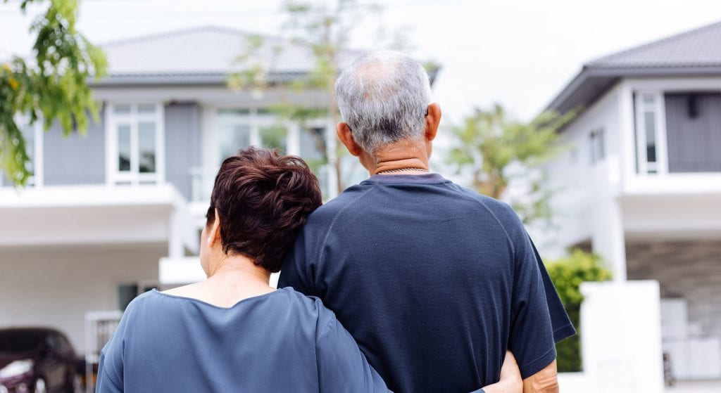 Back of couple standing in front of home, loan forbearance for senior homeowners