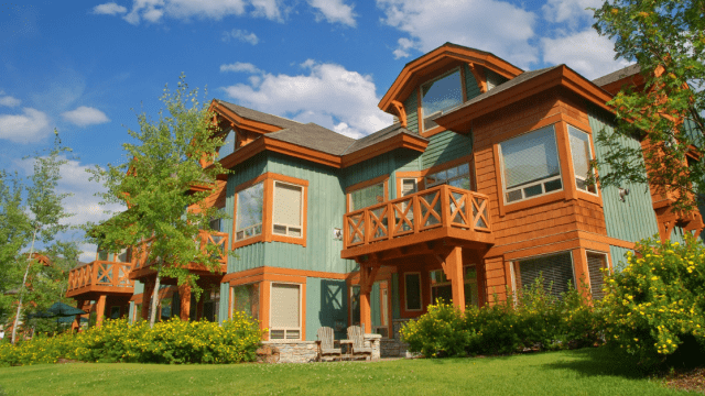 Green and brown vacation home with grass lawn